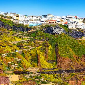 Bergpad naar de stad Fira, groene bergen en gekleurde huizen