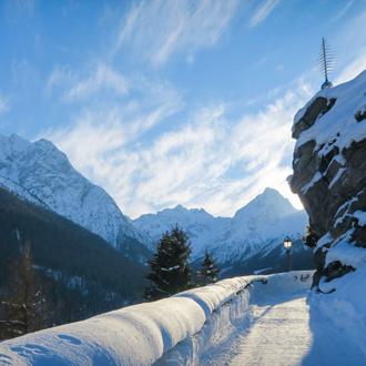 Prachtig besneeuwd wit looppad in de bergen. Met bergen in de verte.