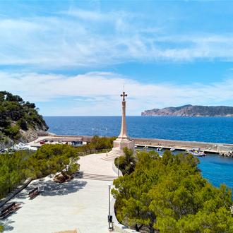 Standbeeld in Santa Ponsa met groene bomen en blauwe zee.