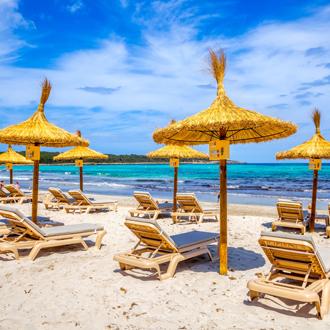 Foto van strand van Sa Coma met ligbedjes en parasols
