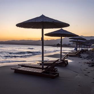 Zonsondergang op het strand van Stalis met zonebedden en parasols