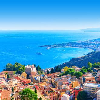 Gekleurde huizen van de stad Taormina. Uitkijkend over azuurblauwe zee