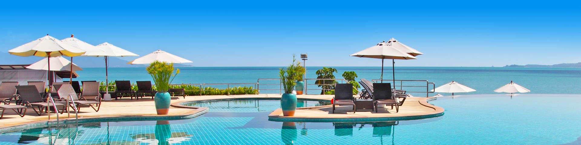 Zwembad met ligbedjes en parasols in luxe resort