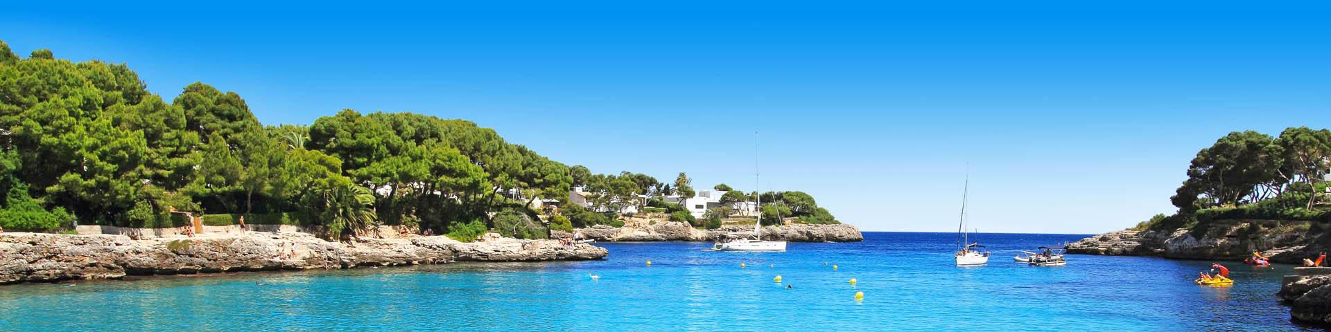 Bootje in de zee bij de rotsen van Cala d'Or op Mallorca