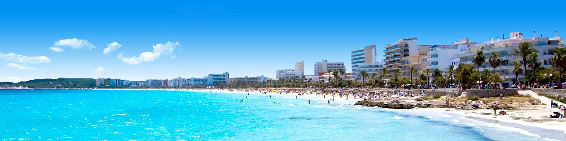 Uitzicht op toeristisch strand bij Cala Millor op Mallorca met de stad op de achtergrond