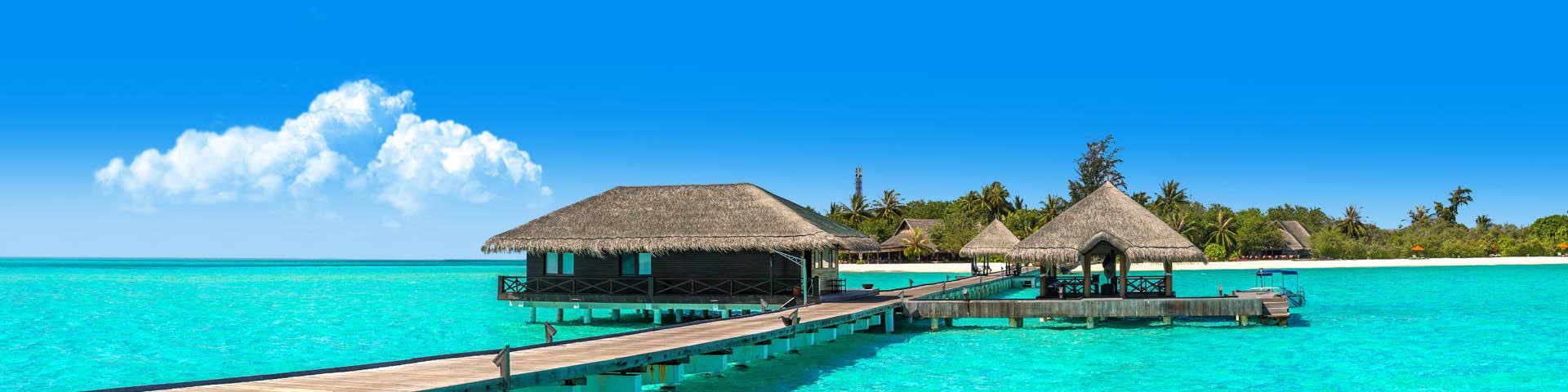 Luxe accommodatie gelegen in de helderblauwe zee met een strand op de achtergrond in de Malediven
