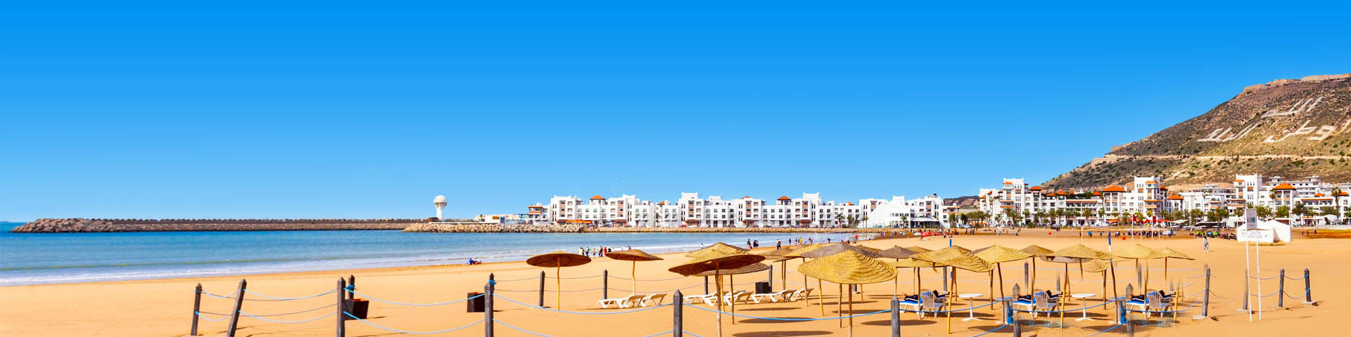 Goudgeel zandstrand met parasols, de zee en witte huizen op de achtergrond in Marokko