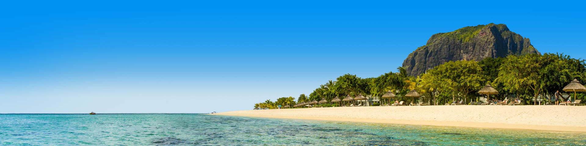 Zee met zandstrand en palmboom parasols op Mauritius