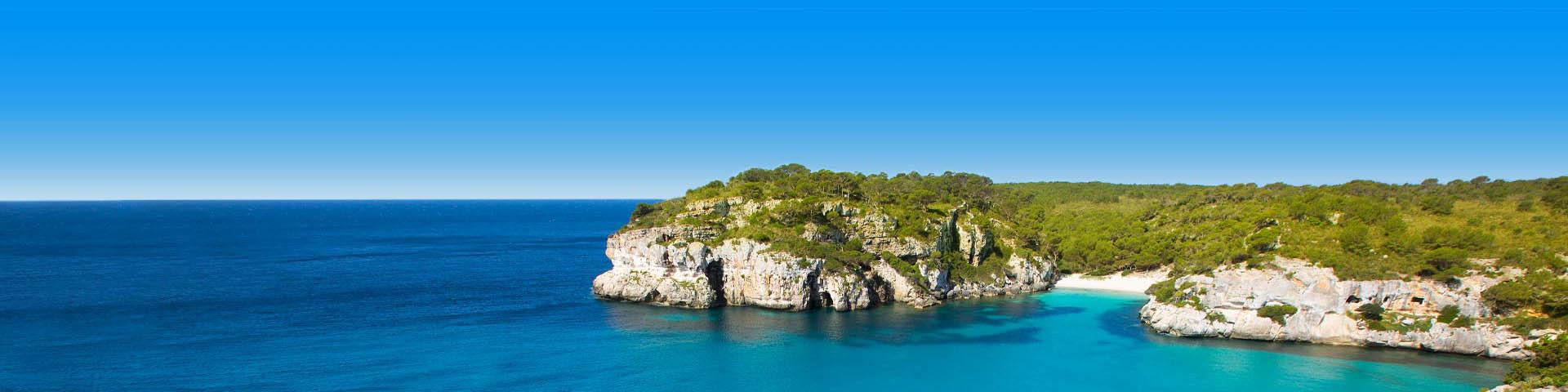 Helderblauwe zee grenzend aan rotsen bij het Spaanse eiland Menorca