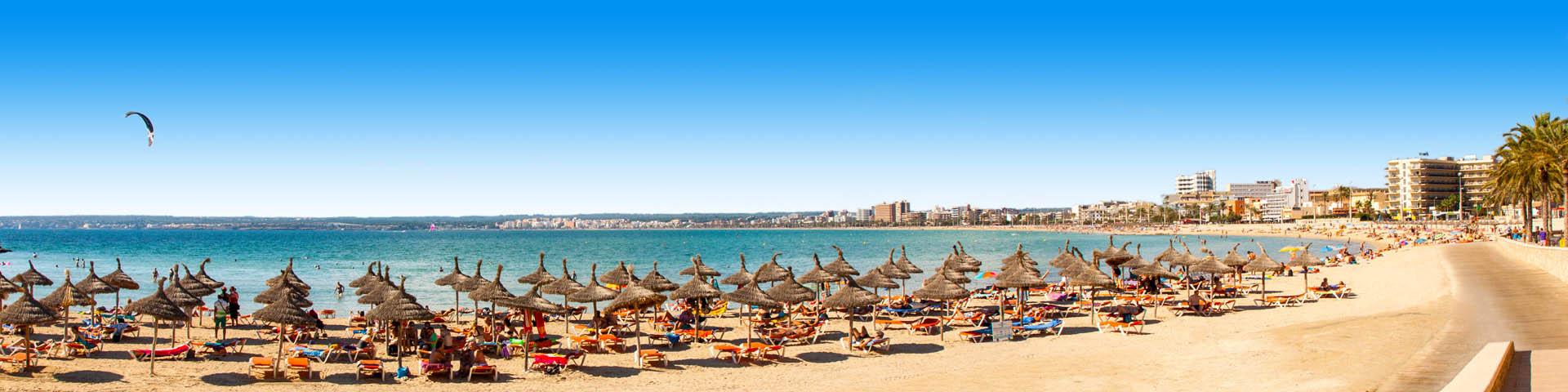 Ligbedjes met parasols op het strand van Playa de Palma op Mallorca