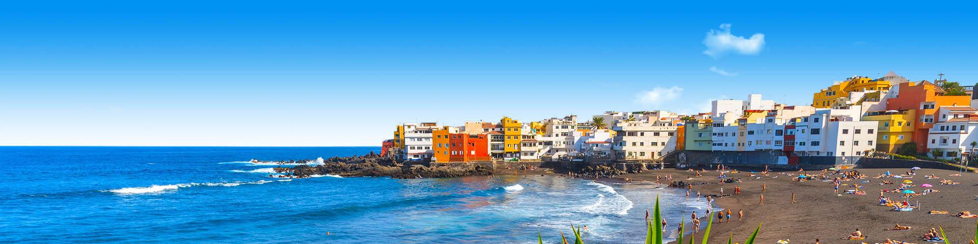 De zee en gekleurde huisjes in Puerto de la Cruz