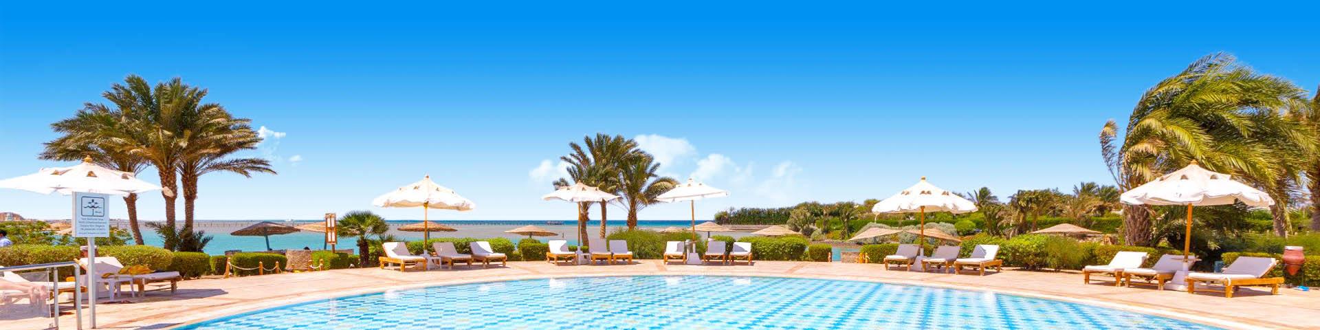 Hotel met zwembadbadcomplex, zwembad, ligbedden en palmbomen