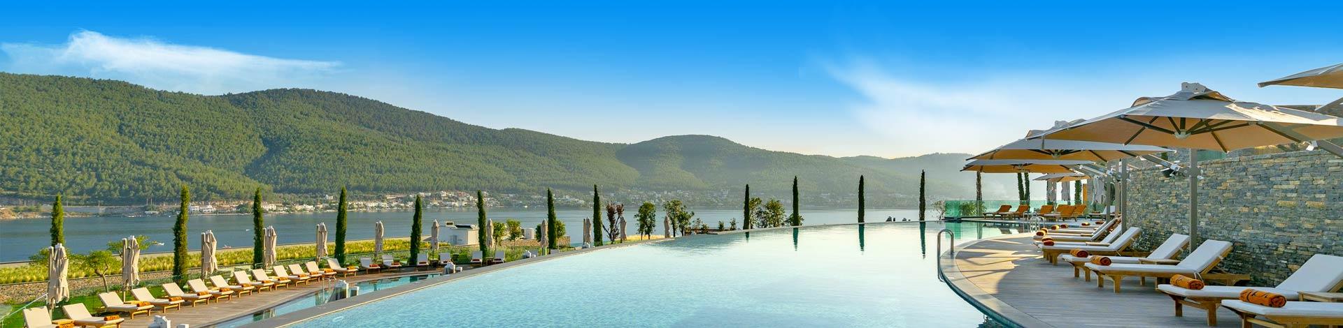Prachtig luxe zwembad met ligbedjes met heuvels en de zee aan de kust van Turkije