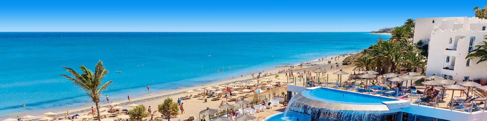 Uitzicht op het zandstrand en helderblauwe zee bij een Allsun hotel