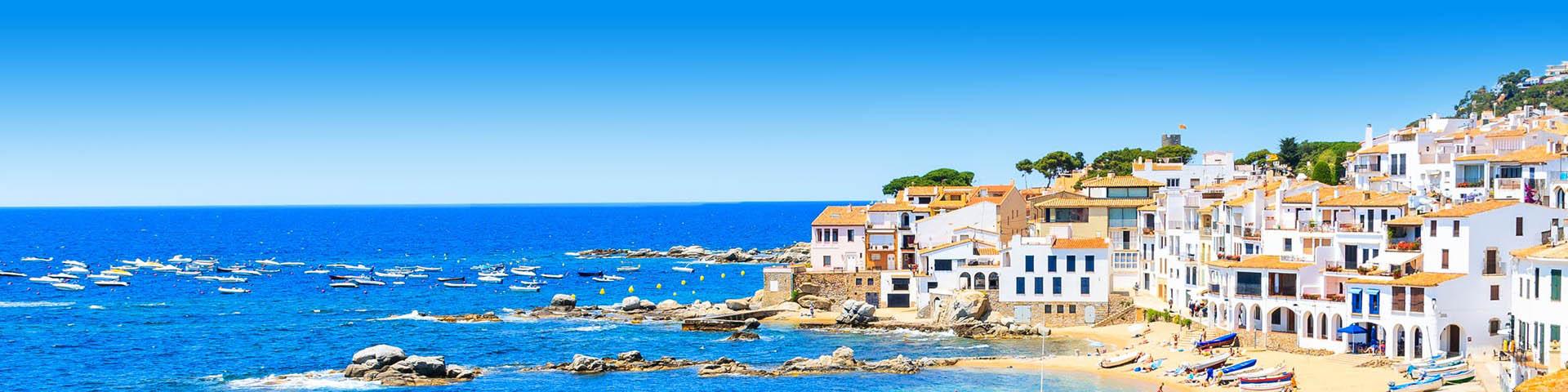 Sppanse kust met witte huisjes en blauwe zee.