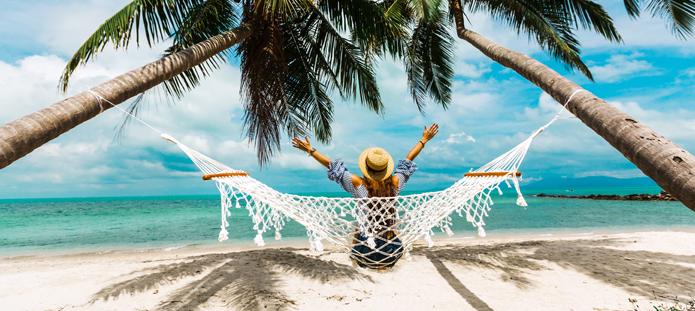 Vrouw in hangmat tussen palmbomen op vakantie