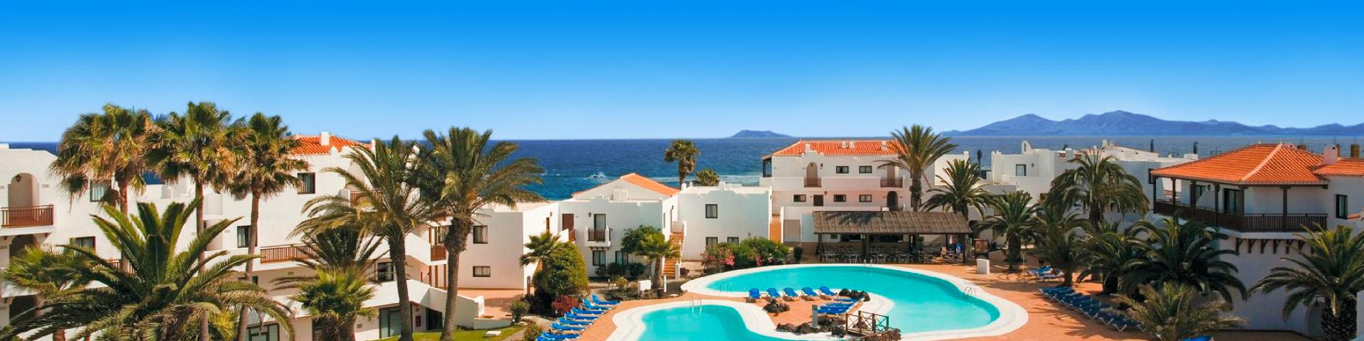 Hotel met witte kamers en oranje daken met 2 zwembaden en zee op de achtergrond