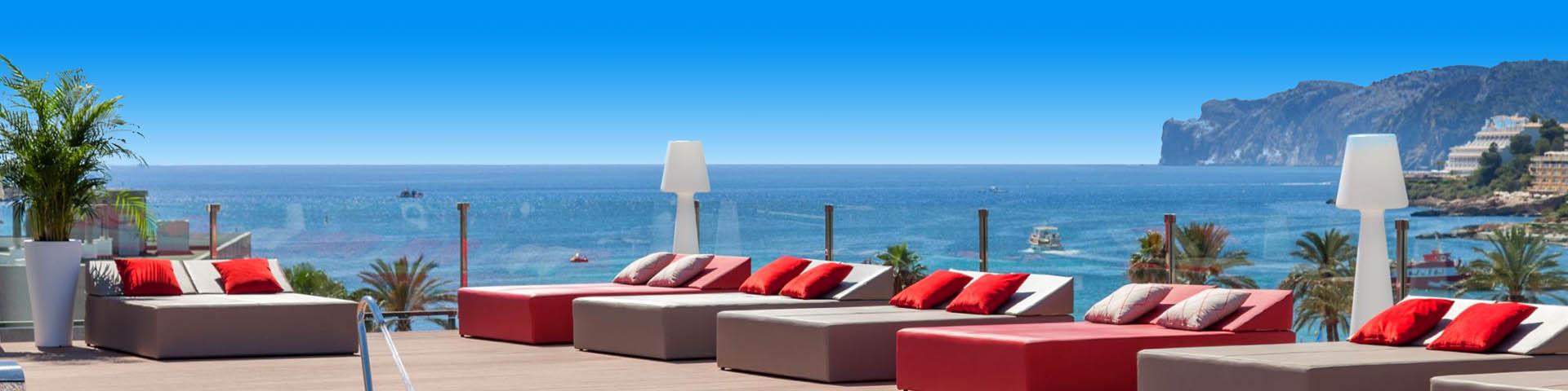 Ligbedden met kussens met uitzicht op de zee bij een Zafiro hotel