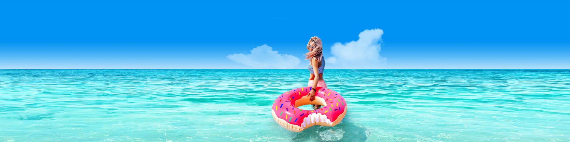 Jonge vrouw in de zee met roze opblaasdonut