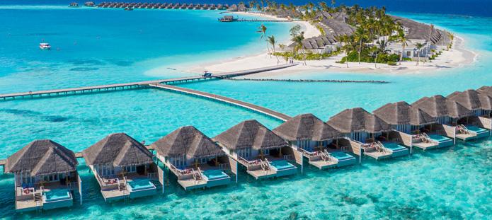 Helderblauwe zee bij de Malediven met waterbungalows op palen in zee met rieten daken