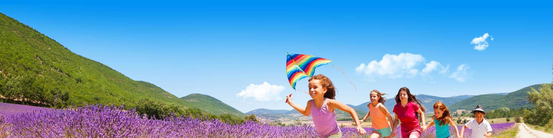 Rennende kinderen met een vlieger in de hand tijdens de kampeervakantie in een mooie omgeving
