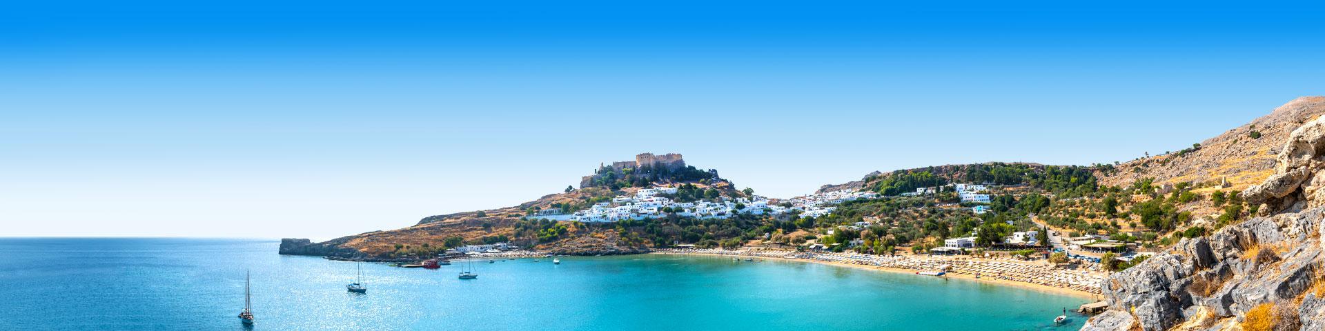 Een berg en blauw zeewater met bootjes tijdens de paasvakantie Rhodos