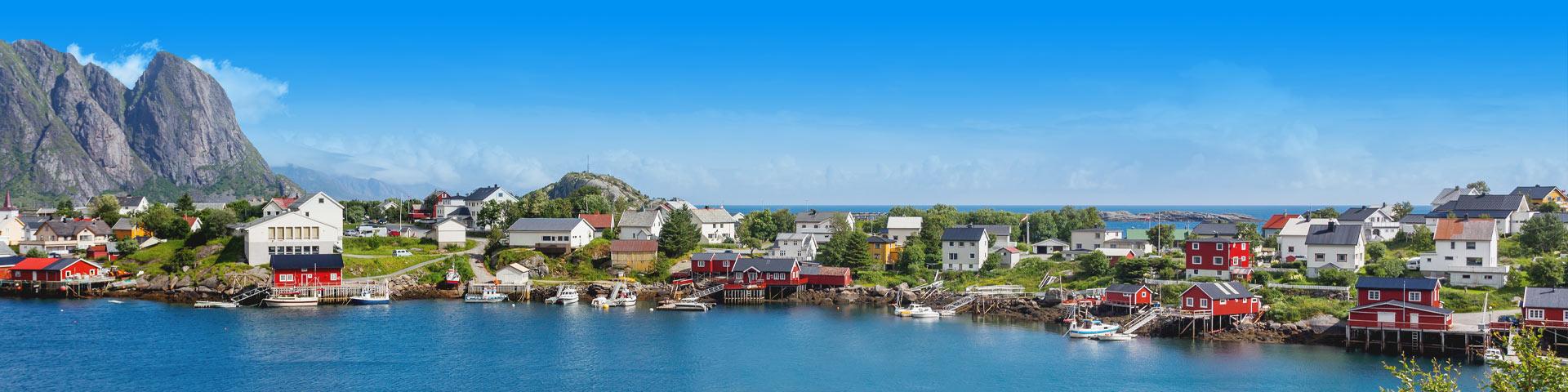 Typische houten huisjes aan een meer omringd door bergen in Scandinavië