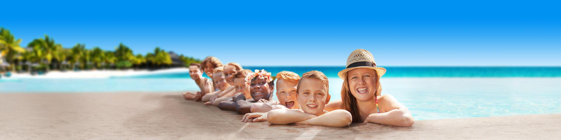 Kinderen aan de rand van het zwembad op vakantie