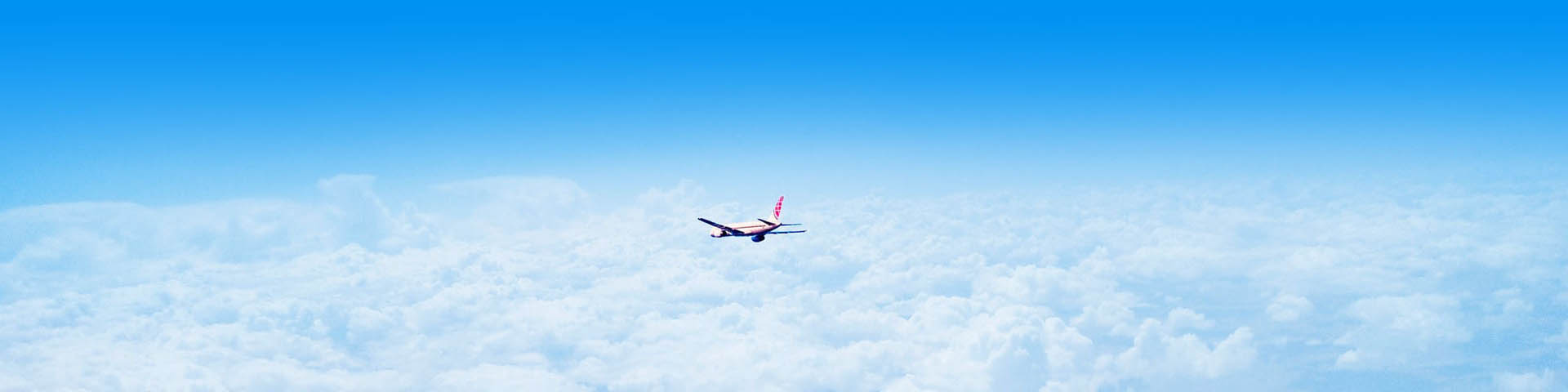Vliegtuig vliegt boven de wolken in de hemelblauwe lucht