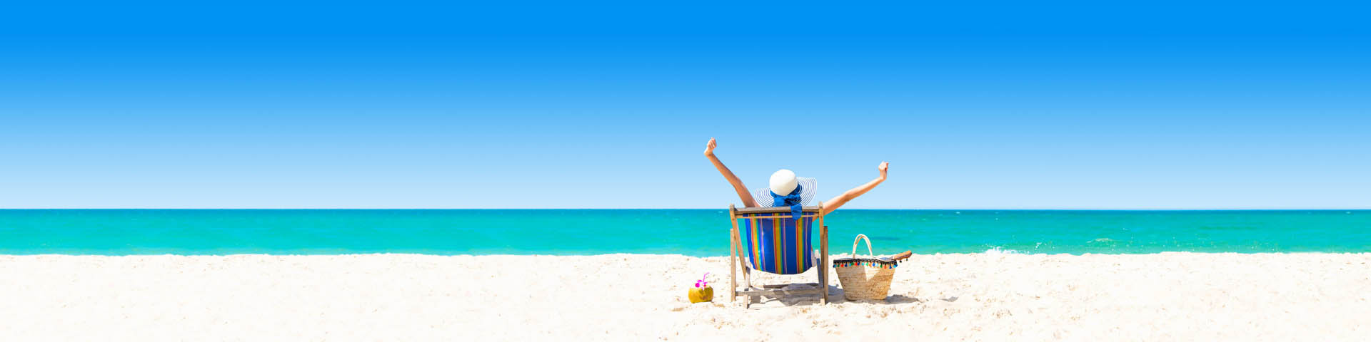 Wit zandstrand met azuurblauwe zee en vrouw zittend in strandstoel