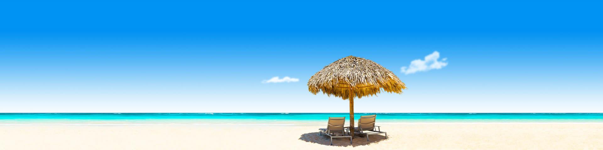 Ligbedjes met parasol op een wit zandstrand met blauwe zee