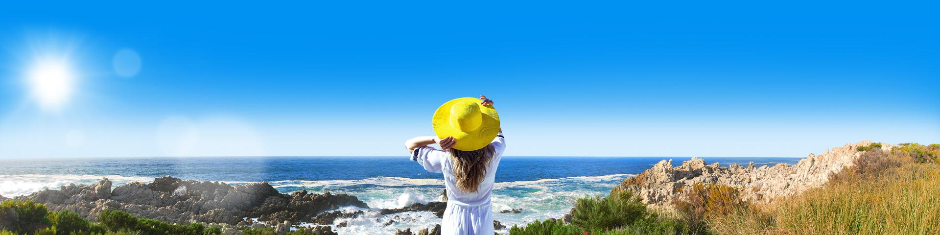 vrouw op een balkon die uitkijkt over het strand