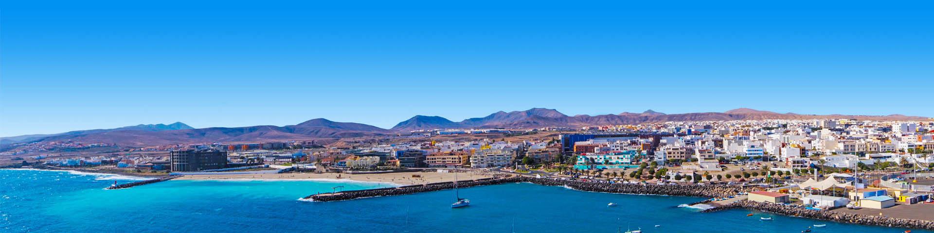 KPrachtige strand met blauwe zee en uitkijkend over een dorp en bergen op de Canarische Eilanden.