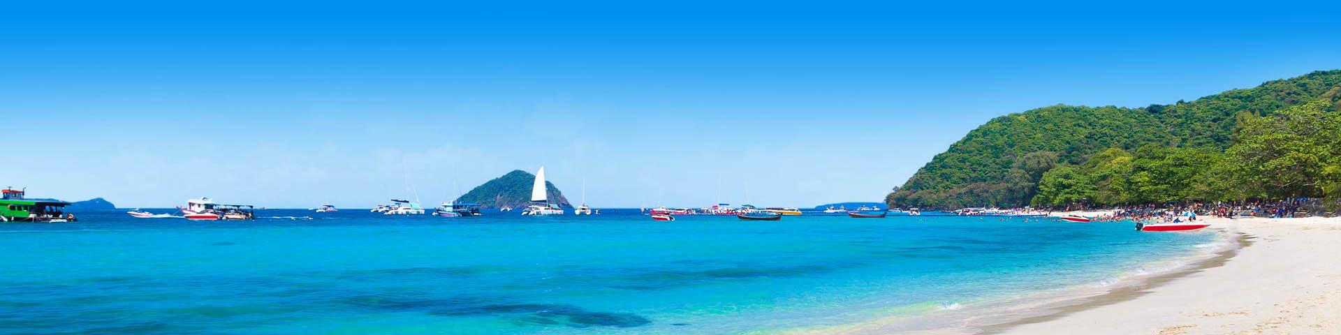 Wit strand met prachtig helderblauwe zee en vissersbootjes