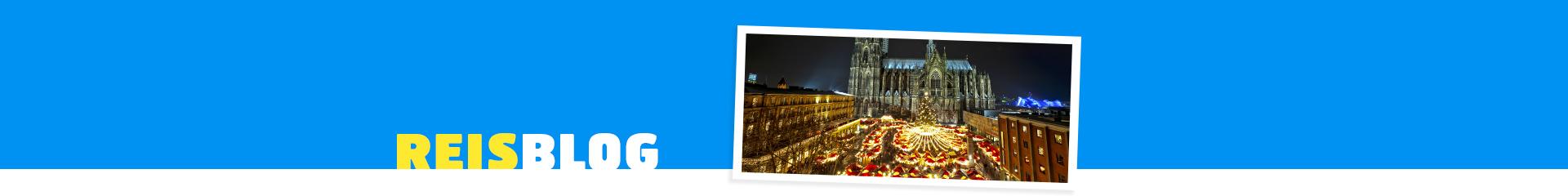 Straat versierd in kerstsferen, met veel lichtjes en een mooie kerk op de achtergrond.