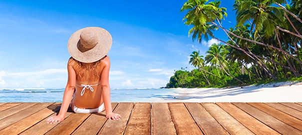 Vrouw met hoed op een tropische vakantiebestemming met palmbomen en wit strand