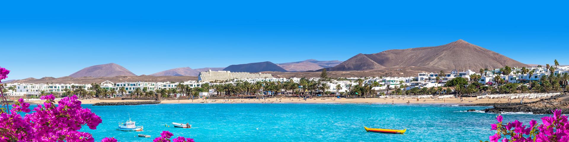 Uitzicht op de kust van Lanzarote met heuvellandschap en witte huisjes aan het strand
