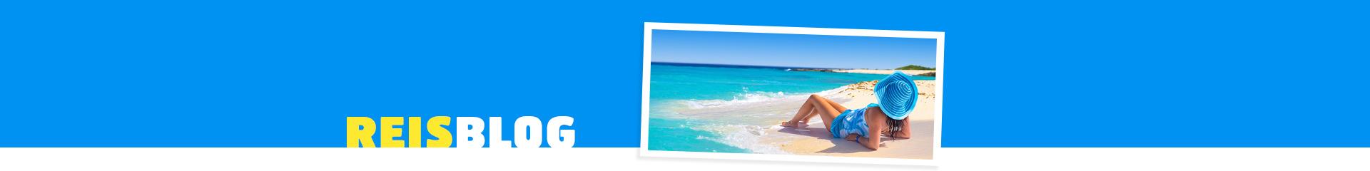 Vrouw ligt op een wit zandstrandmet uitzicht opde azuurblauwe zee.