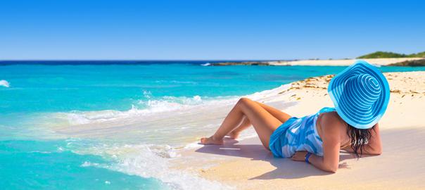 Helderblauwe zee met vrouw op het strand