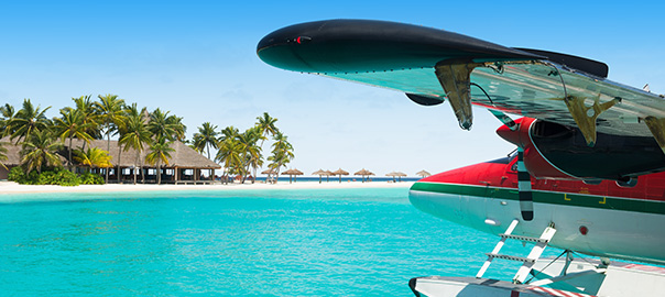 Vliegtuig, helderblauwe zee, palmbomen en een hagelwit zandstrand