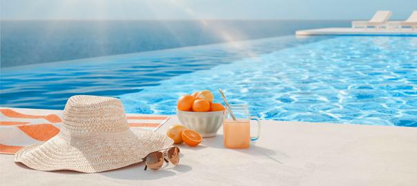 Hoed, zonnebril en lekker drankje bij het zwembad op vakantie
